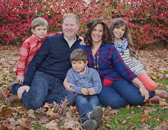 Family with three children wearing blue and red outfits in a fall outdoor photo shoot.