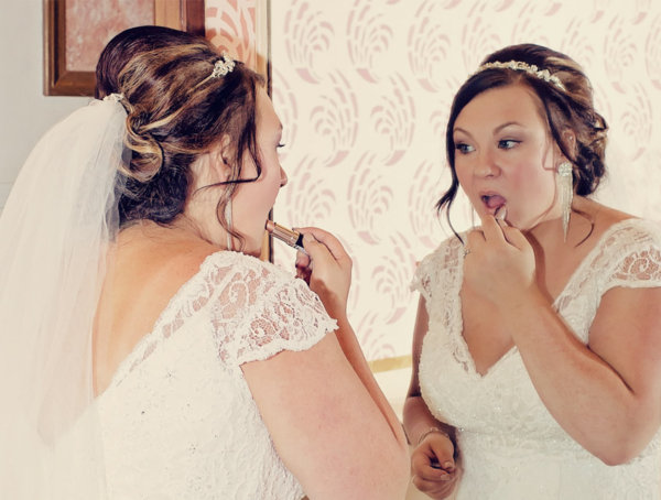 Bride applying her makeup during her wedding preparation