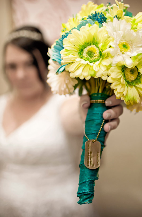 Close-up photograph of the wedding flowers with symbolic dog tags around them, with the bride out of focus in the background.