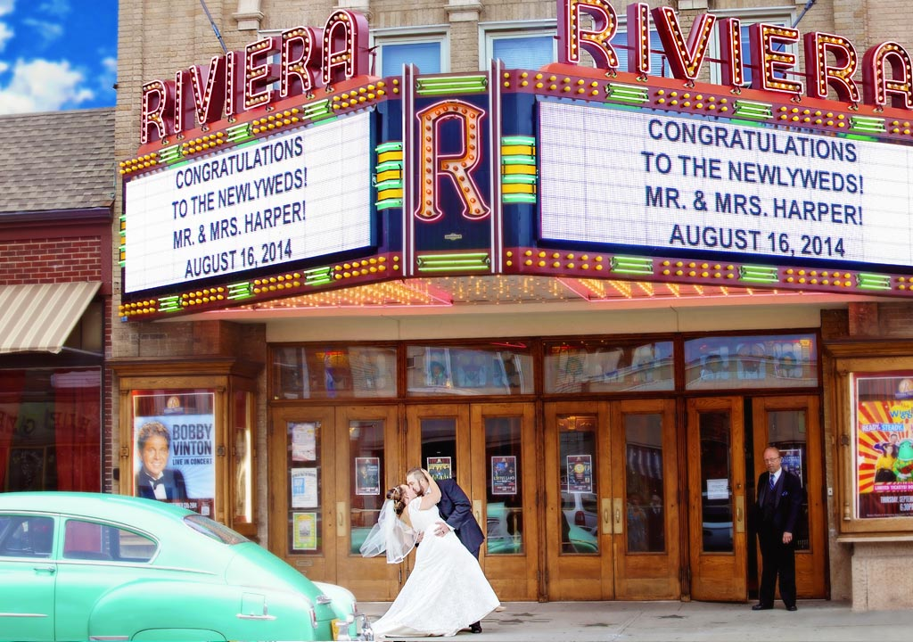 Beautiful retro looking wedding photograph of the bride and groom kissing with their names in the marquee and a vintage green car in the foreground.