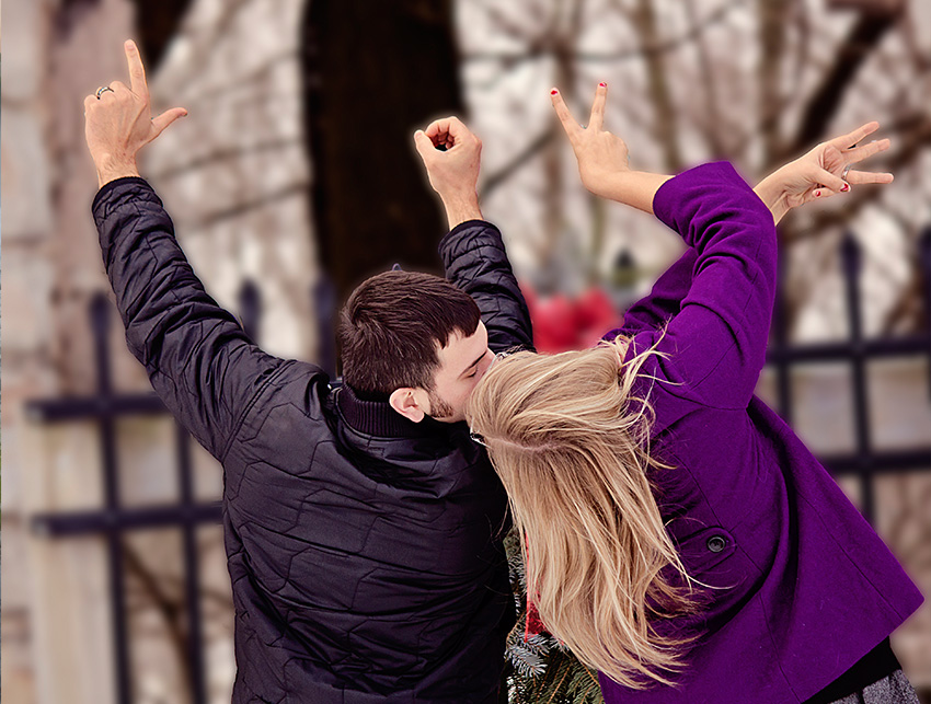 """Couple during their engagement shoot facing away form the camera, forming the word """"love"""" with their hands."""
