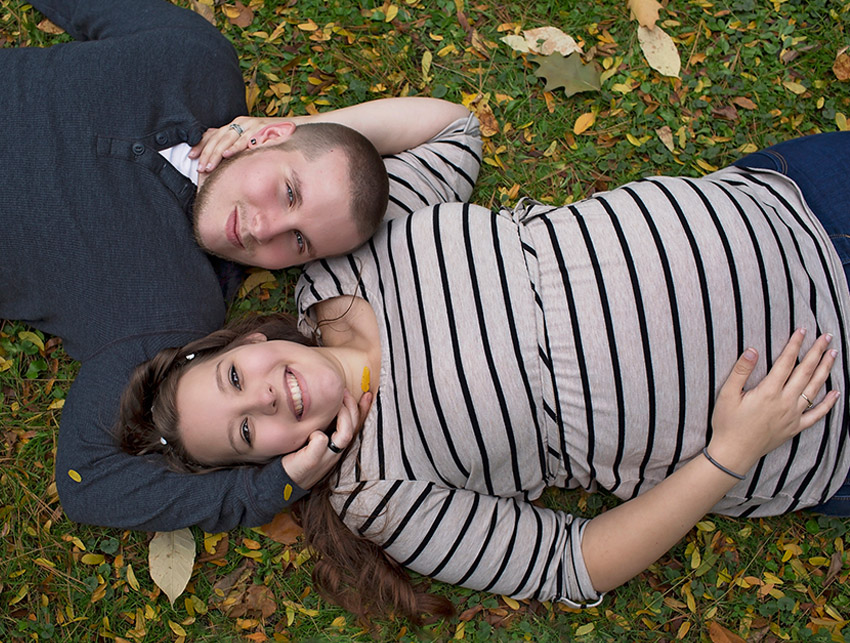 Happy expecting parents laying the grass for a maternity photography session