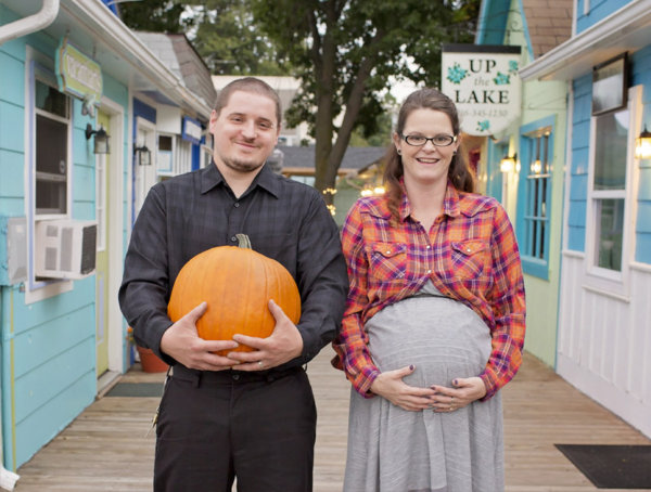 Funny staged fall maternity photo with the mom to be holding her baby belly and the new dad to be holding a pumpkin in the same way