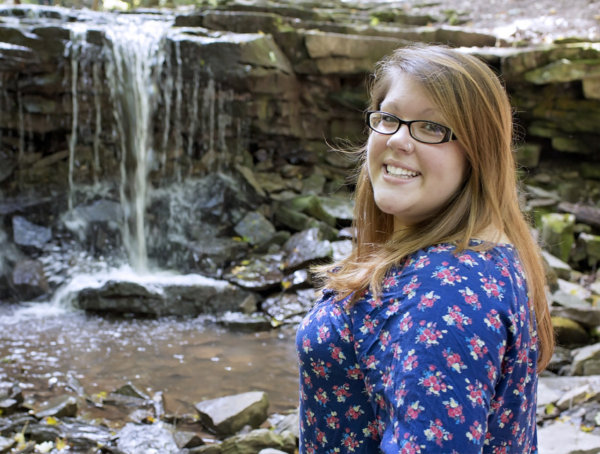 Lovely young lady in blue with small natural waterfall in the background