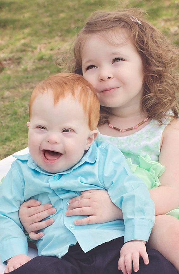 Toddler boy, and his big sister smiling big at the camera