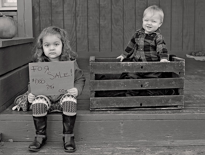 Uninthused older sister holding a For Sale! sign for her brother who is smiling in an old style basket on a porch