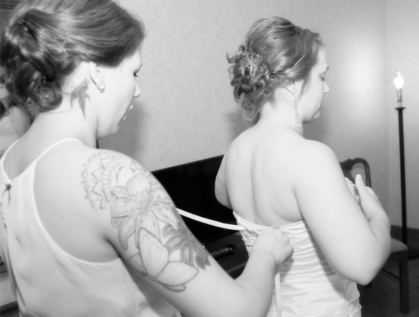 Wedding gown being laced up by bridesmaid with tattoo's on her arm and neck.