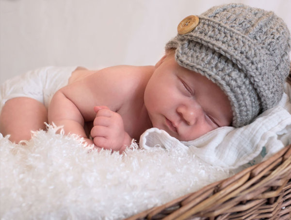 Photo of a newborn boy with a gray knit hat, on cheesecloth in a basket
