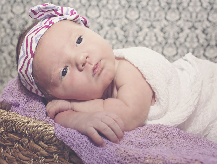 Newborn baby girl with purple striped headband and a purple cheesecloth liner in a basket