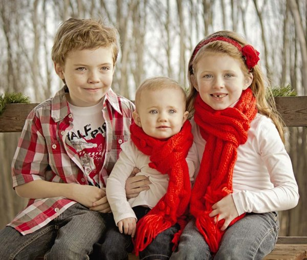 Siblings wearing matching red accessories for a fall photo session.