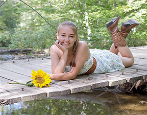 young woman on a foot bridge with sunflower and cowboy boots for her senior pictures