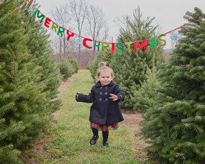 Little girl running through a Christmas tree farm