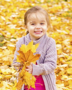 Young girl in the fall playing with bright leaves in her hands.